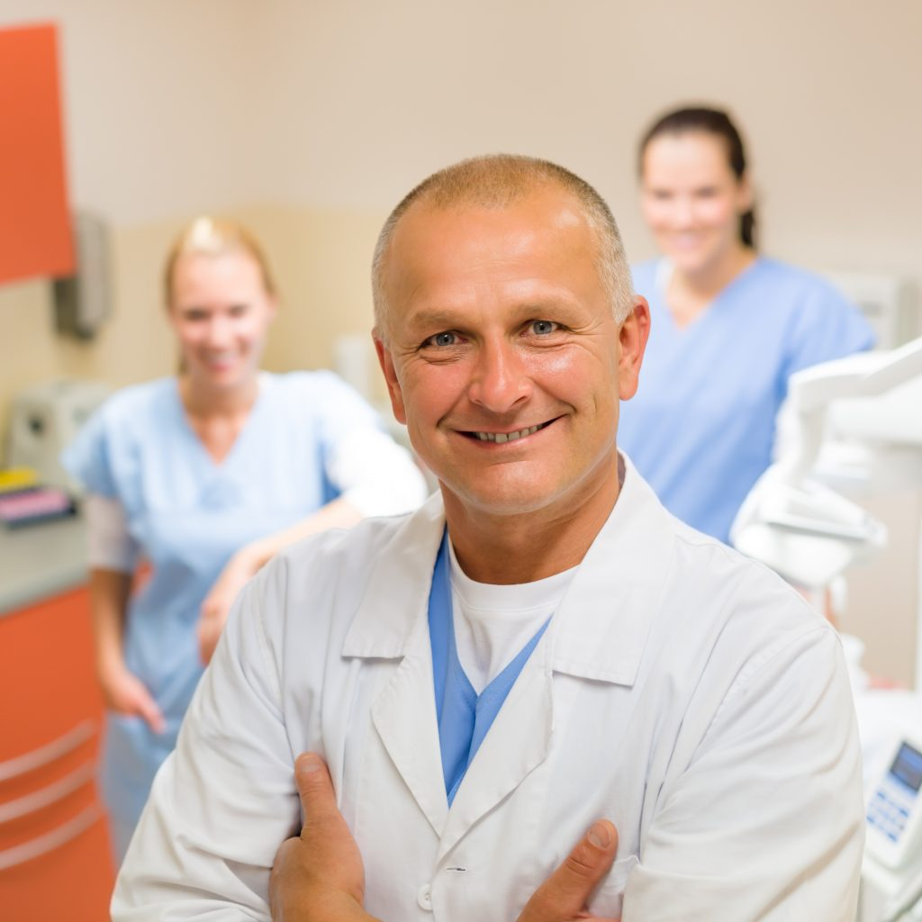 Smiling male dentist posing with female assistants at office